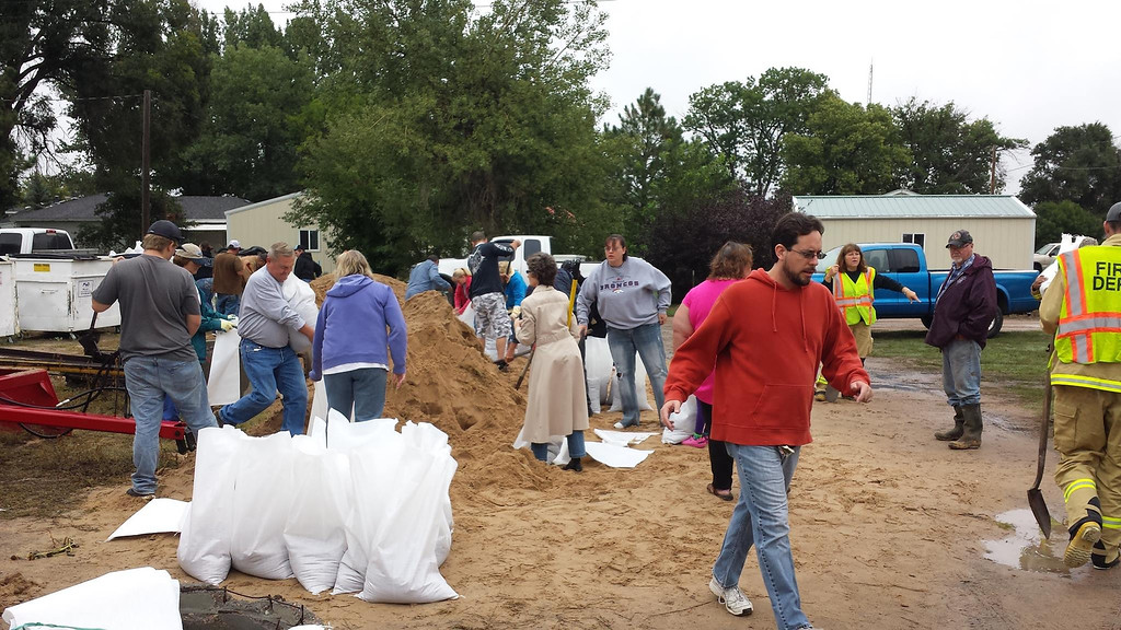 Description of . Merino-area residents fill sandbags Sunday in preparation for flooding from the South Platte River. Merino was later evacuated.